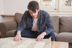 Young man. At his living room with a plaid shirt and a map Royalty Free Stock Photos