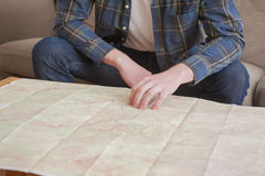 Young man. At his living room with a plaid shirt and a map Royalty Free Stock Photo