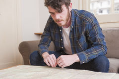 Young man. At his living room with a plaid shirt and a map Royalty Free Stock Images