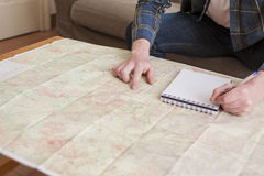 Young man. At his living room with a plaid shirt and a map Stock Photo