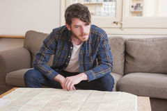 Young man. At his living room with a plaid shirt and a map Royalty Free Stock Image