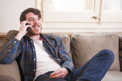 Young man. At his living room with a plaid shirt on the phone Stock Images