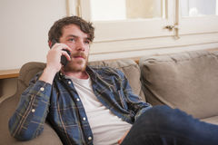 Young man. At his living room with a plaid shirt on the phone Stock Image