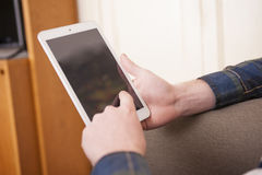 Young man. At his living room with a plaid shirt and a tablet Royalty Free Stock Photo