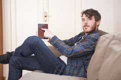Young man. At his living room with a plaid shirt and a tablet Stock Images