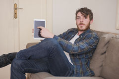 Young man. At his living room with a plaid shirt and a tablet Stock Photography