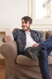 Young man. At his living room with a plaid shirt and a tablet Royalty Free Stock Image