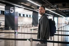 Young man with his luggage and backpack using smartphone while waiting for airline flight in the international airport stock photography