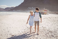 Young man with his mother walking on sand at beach Royalty Free Stock Photos