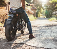 Young man on his motorcycle on dirt road Stock Images