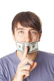 Young man with his mouth sealed by a hundred dollar bills  Stock Images