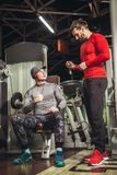 Young man and his personal fitness trainer in the gym. Young men and his personal fitness trainer in the gym exercising Royalty Free Stock Photo