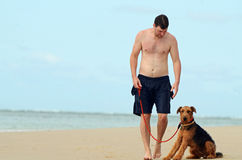 Young man & his pet dog walking on island beach Royalty Free Stock Image