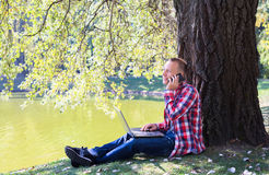 Young man with his phone and laptop in city park outdoor. Man in red short smiling Stock Photos