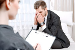Young man with his psychologist Royalty Free Stock Images