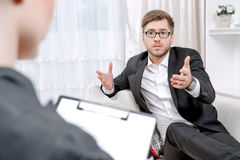 Young man with his psychologist Stock Image