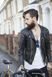 Young man in his 20s or early 30s with bicycle Royalty Free Stock Image