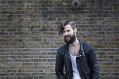 Young man in his 20s or early 30s in front of brick wall sminlin Stock Photography