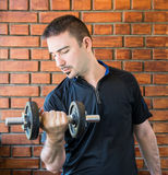 Young man in his 30s pulling dumbell Stock Image