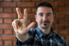 Young man  in his 30s showing three fingers. Selective focus. Young man in plaid shirt with trim beard in his 30s showing three fingers. Selective focus Royalty Free Stock Images