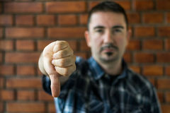 Young man in his 30s showing thumbs down. Selective focus royalty free stock photography