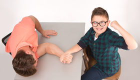 Young man and his son arm wrestling. Boy in glasses looking so strong. He and his dad are competing in physical strength. People sitting at the table and arm Royalty Free Stock Images