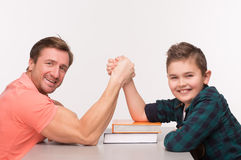 Young man and his son arm wrestling. Photo of little boy and his dad competing in physical strength. Young men and his son arm wrestling Royalty Free Stock Image