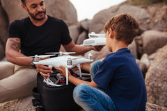 Young man with his son at the beach with a drone. Outdoor shot of young men with his son at the beach with a drone. Father and son at the sea shore with drone Royalty Free Stock Photo