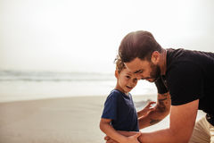 Young man with his son at the beach. Outdoor shot of young men with his son at the beach. Father and son on sea shore during summer vacation stock photo