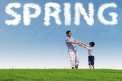 Young man with his son at the field. Happy asian father holding hands with his son on the green meadow under a spring cloud Royalty Free Stock Photo