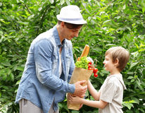 Young man and his son with a paper bag shopping organic natural food Royalty Free Stock Photo