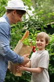 Young man and his son with a paper bag shopping organic natural food Royalty Free Stock Images
