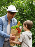 Young man and his son with a paper bag shopping organic natural food Stock Images