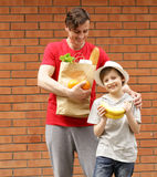 Young man and his son with a paper bag shopping organic natural food Stock Image