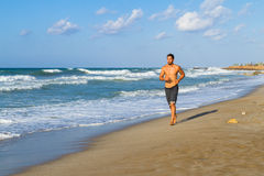 Young man in his twenties jogging on a sandy beach Stock Image