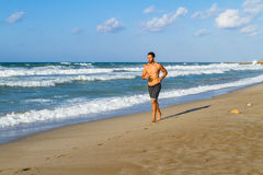 Young man in his twenties jogging on a sandy beach Stock Photos