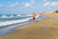 Young man in his twenties jogging on a sandy beach Royalty Free Stock Photo