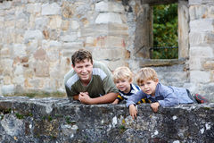 Young man and his two little boys standing behind wall of old Ge Stock Photography