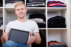 Young man with his wardrobe Stock Image