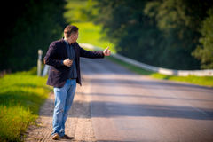 Young man hitch-hiking Stock Images