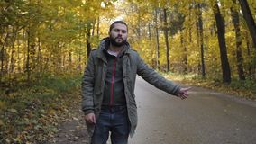 Young man hitchhiker with standing on a highway in autumn. Adventure and tourism concept. The driver jokes shows middle finger stock video