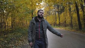 Young man hitchhiker with standing on a highway in autumn. Adventure and tourism concept.  stock video footage