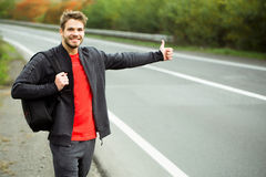 Young man hitchhiking Stock Photography