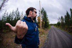 Young man hitchhiking on a finnish country road near the woods Stock Photos