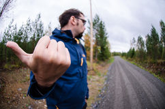 Young man hitchhiking on a finnish country road near the woods Stock Photography