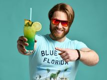 Young man hold blue hawaiian margarita cocktail drink juice happy smiling pointing one finger. Over blue mint background stock image