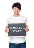 Young man hold with chalkboard showing phrase of semester start Stock Image