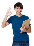 Young man hold with clipboard and ok sign gesture Royalty Free Stock Photos