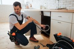 Young man hold hose in hand. Bad smell. Stinks. Handyman suffer from it. Opened toolbox and piece of pipe on floor. Young man hold hose in hand. Bad smell royalty free stock image