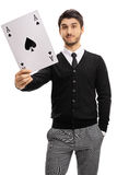 Young man holding an ace of spades card. Isolated on white background Stock Images